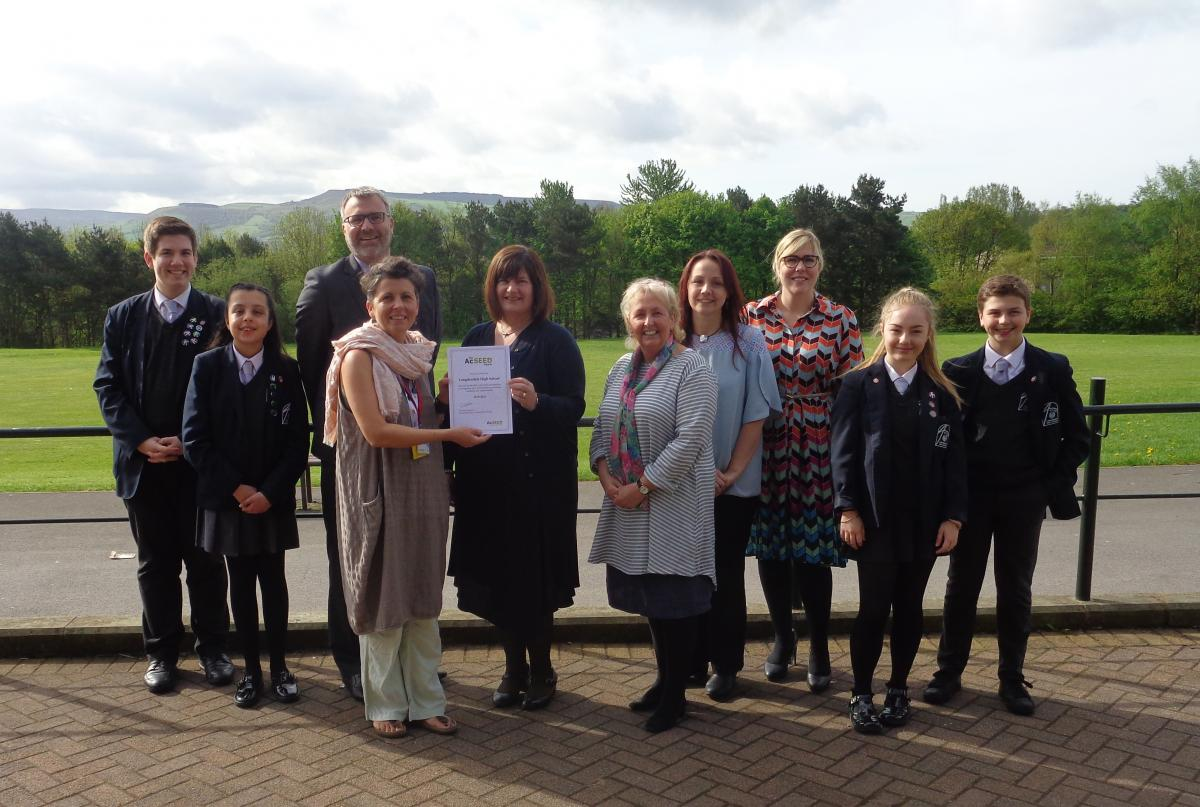 A gathering of students from Longendale High School gathered together with staff from Tameside, Oldham and Glossop Mind posing for a picture with the awarded AcSEED award